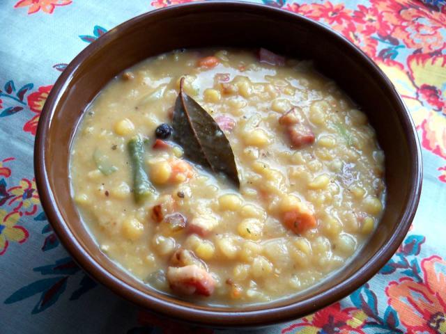 Zupa grochowa nalana dobrązowej, kamionkowej miseczki, którapołożona jest nakwiecistej, zielonkawej serwecie. Wkremowej grochówce pływają kawałki kiełbasy, miękkie ziarna grochu iduży liść laurowy.
