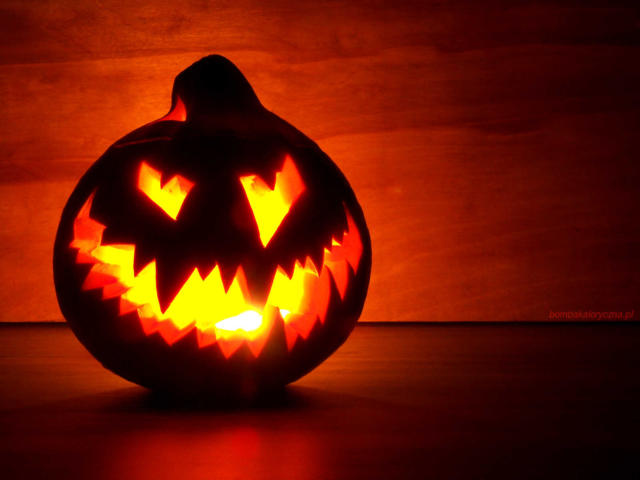 Halloweenowa dynia zwyciętą przerażającą twarzą ipodświetlona odwewnątrz migotliwą świeczką.