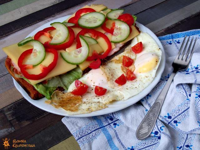 Gofry zpatelni - puszyste, prostokątne gofry zsałatą, szynką, serem żółtym, czerwoną papryką iświeżymi ogórkami. Obok natalerzyku leżą całkowicie ścięte jajka sadzone, posypane ćwiartkami pomidorków koktajlowych.